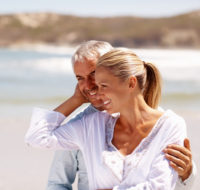 Happy mature couple at the beach for a vacation
