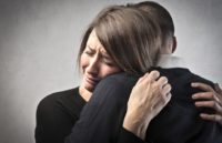 Grieving woman being comforted by trusted friend