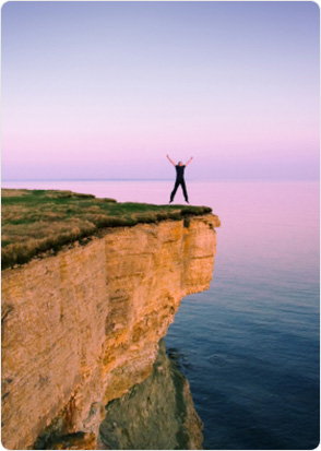 Excited and happy man jumping in the air on a cliff