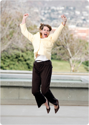 Happy business woman jumping in the air with arms up high