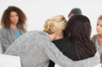 Women in therapy hugging woman friend