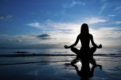 Woman meditating during life coaching on the beach during sunset