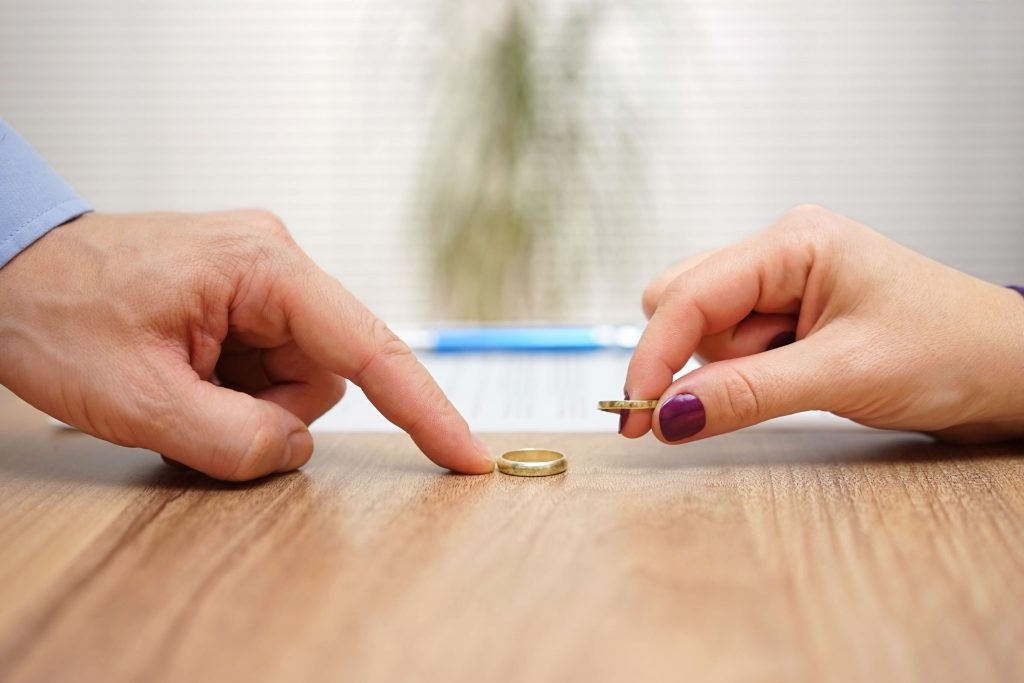 Knowing when to end your marriage. Couple taking off wedding rings.