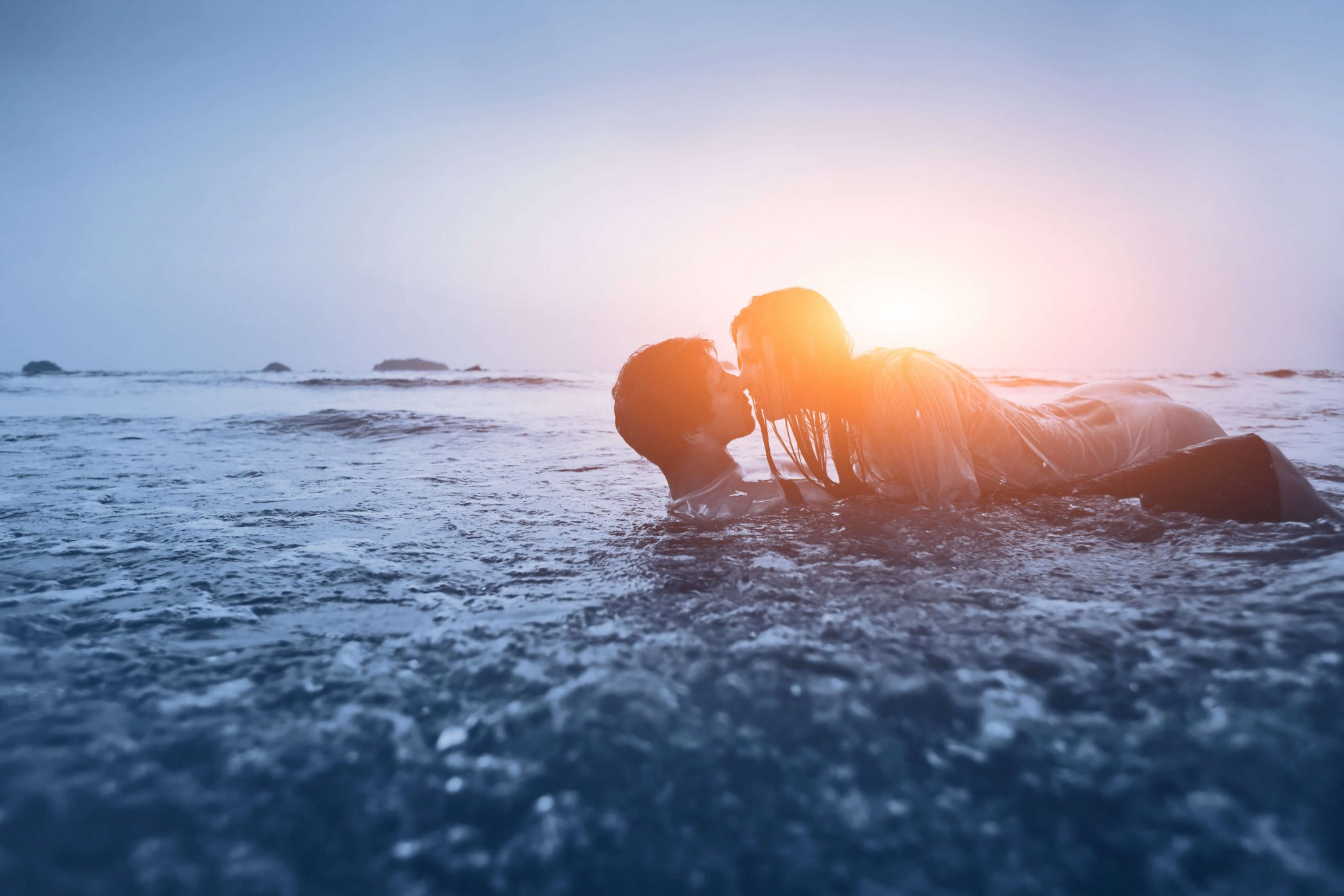 Photo of an intimate couple lying in the water on a beach in the water with the sun rising in the background